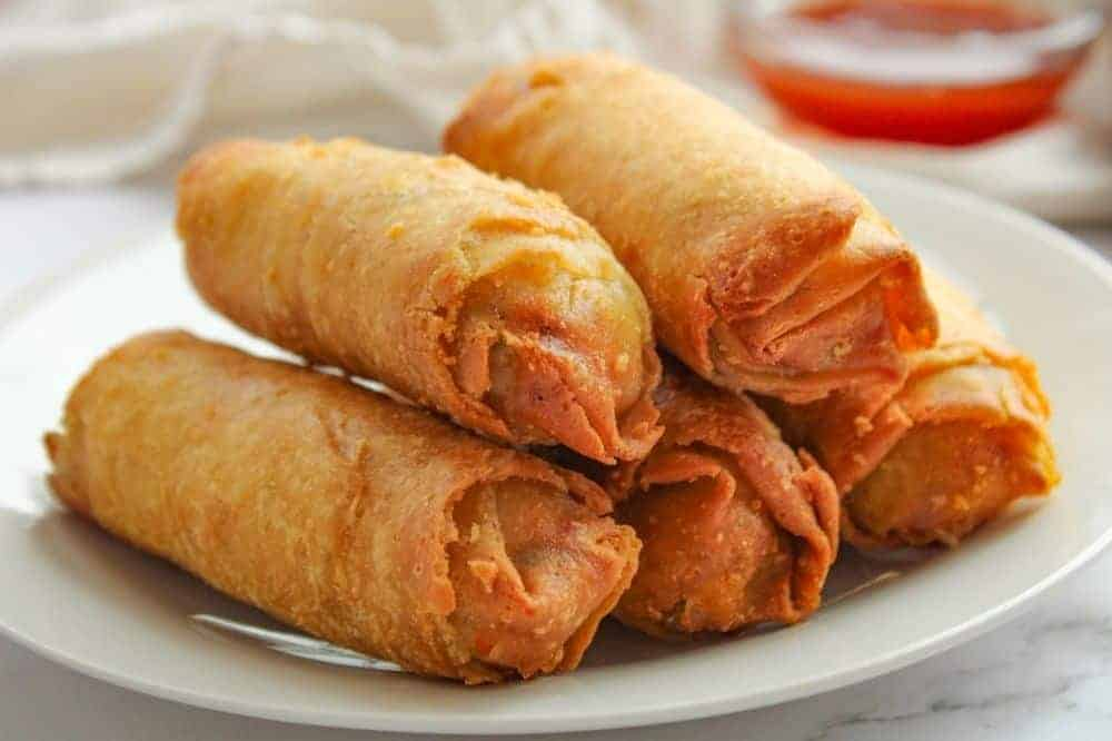 Air Fryer Egg Rolls on a white plate with sauce in a bowl in the background