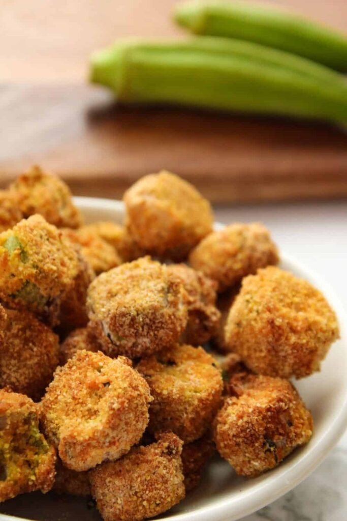 Breaded Air Fryer Okra in a while bowl with full okra in the back