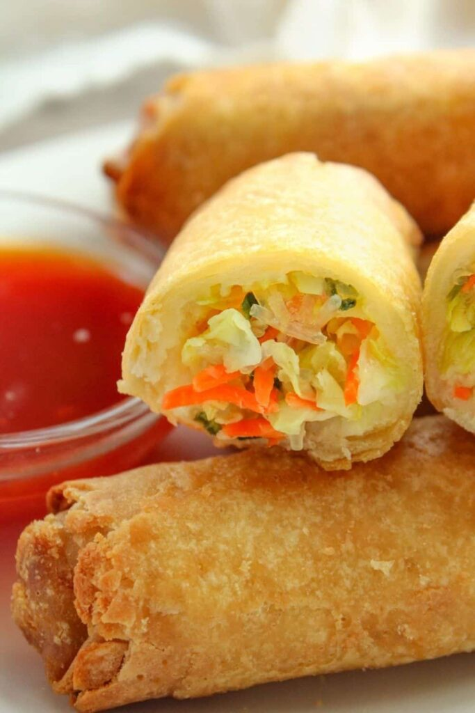 Closeup of frozen egg rolls on a white plate with one cut open and sauce in a small bowl on the side