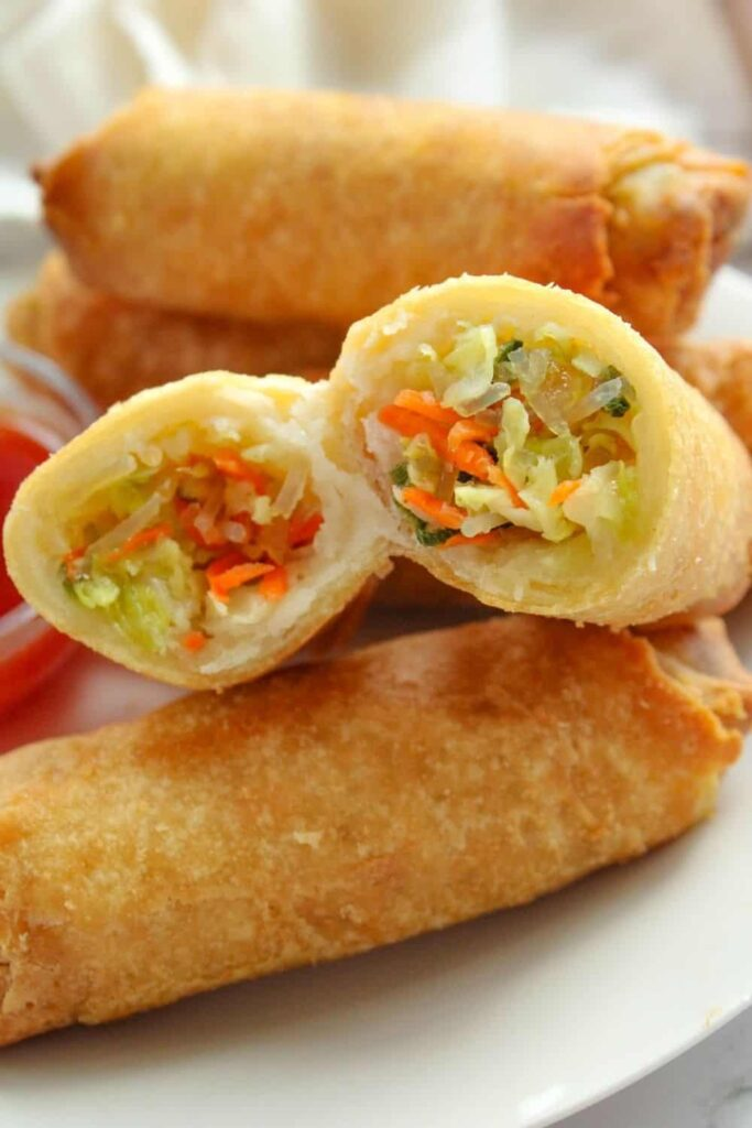 Air Fryer Egg Rolls on a white plate with one cut in half showing the inside