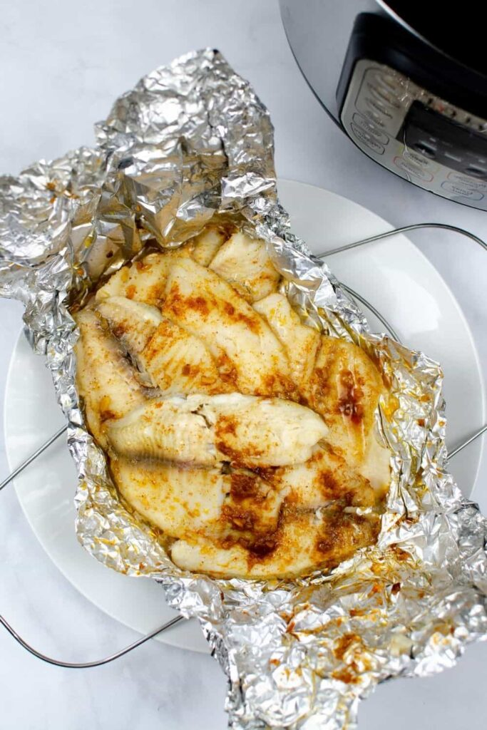 Instant Pot Tilapia with seasoning on top of aluminum foil