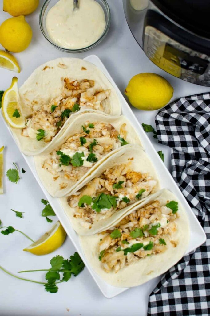 Instant Pot Tilapia Tacos put together in soft shells on a white rectangular serving plate with cilantro sprinkled on top