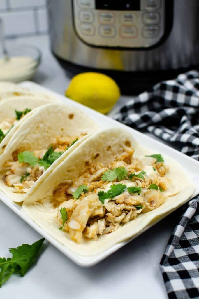 Pressure Cooker Frozen Tilapia served in soft-shelled taco shells on a rectangular white serving dish