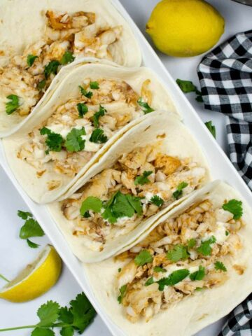 Instant Pot Tilapia assembled in tacos on a rectangular serving plate