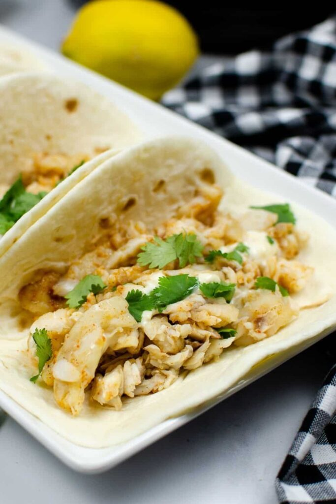 Closeup of Instant Pot Fish Tacos on a white rectangular serving plate with a lemon i nthe background
