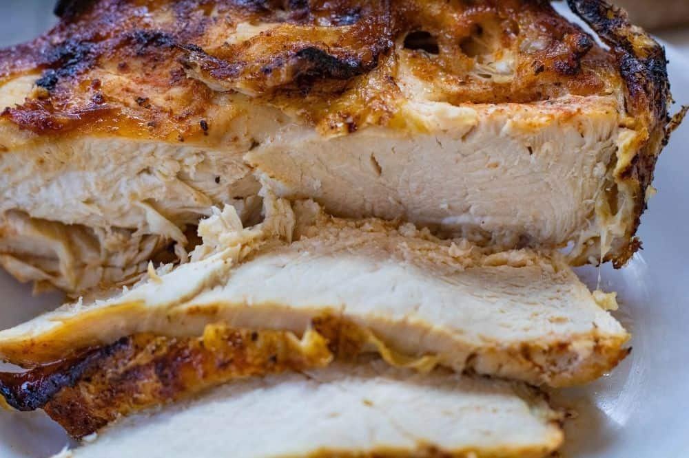 Closeup of air fryer bone-in chicken breasts cut into slices