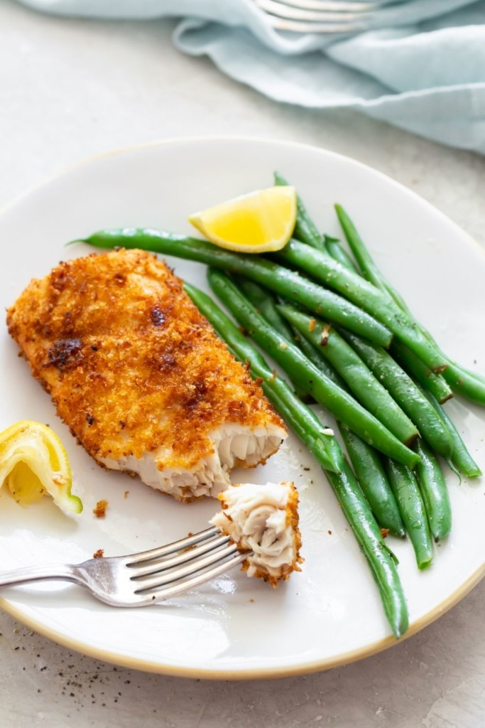 Air Fryer Mahi Mahi on a plate cooked with a piece on the fork and served with green beans and lemon wedges