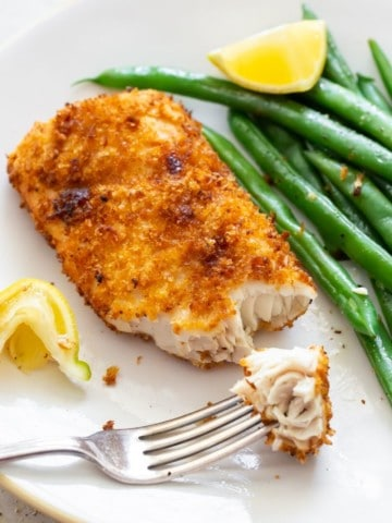 Air Fryer Mahi Mahi with a bite on a fork served with green beans and a slice of lemon