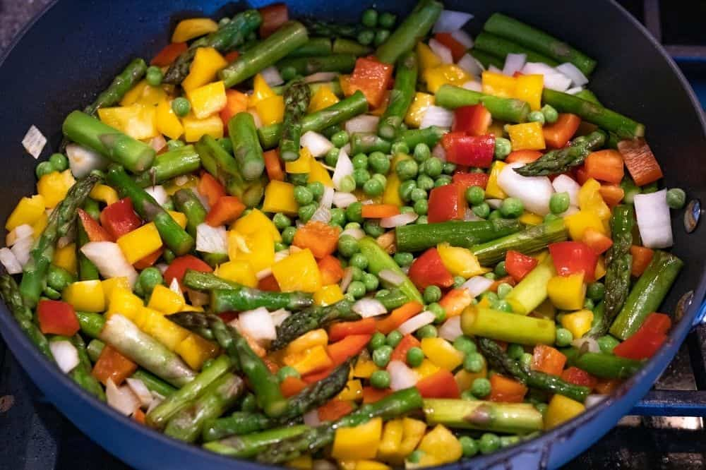 Asparagus, diced sweet peppers, onions, and peas being cooked in a pan