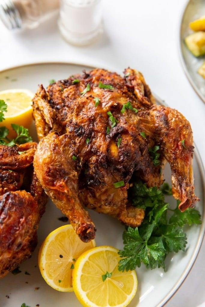 Closeup of one cornish hen served with lemon halves