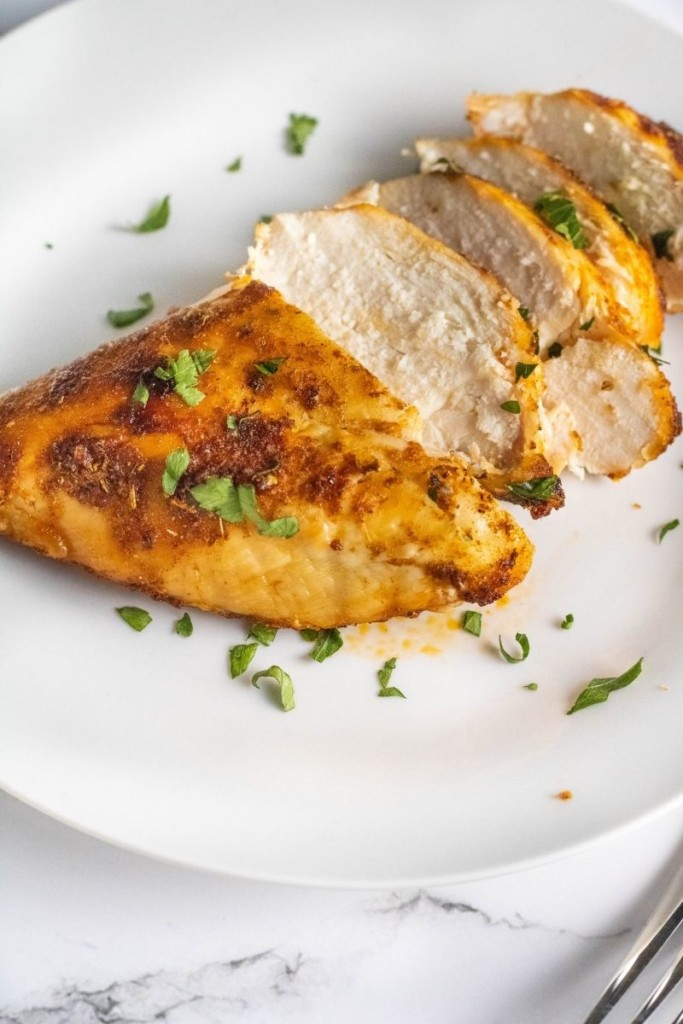Sliced air fryer chicken breasts on a white plate garnished with parsley