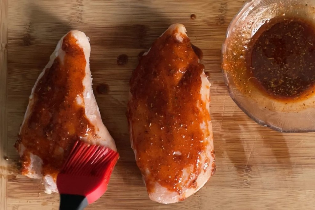 Frozen chicken being basted with spices and oil