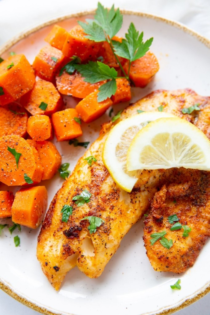Air Fryer Tilapia with lemon sliced on top served with cooked chopped carrots