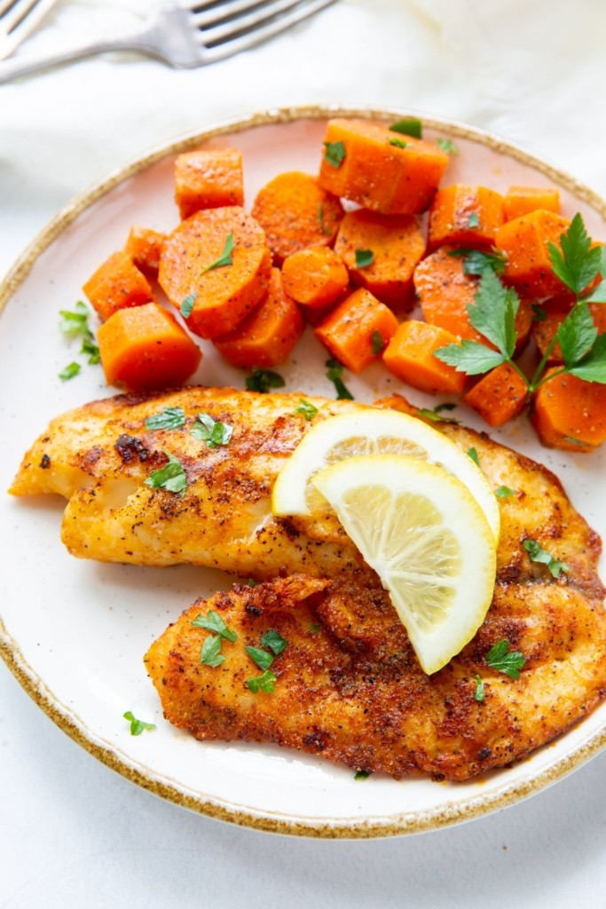 Tilapia on a white plate with lemon wedges and chopped carrots