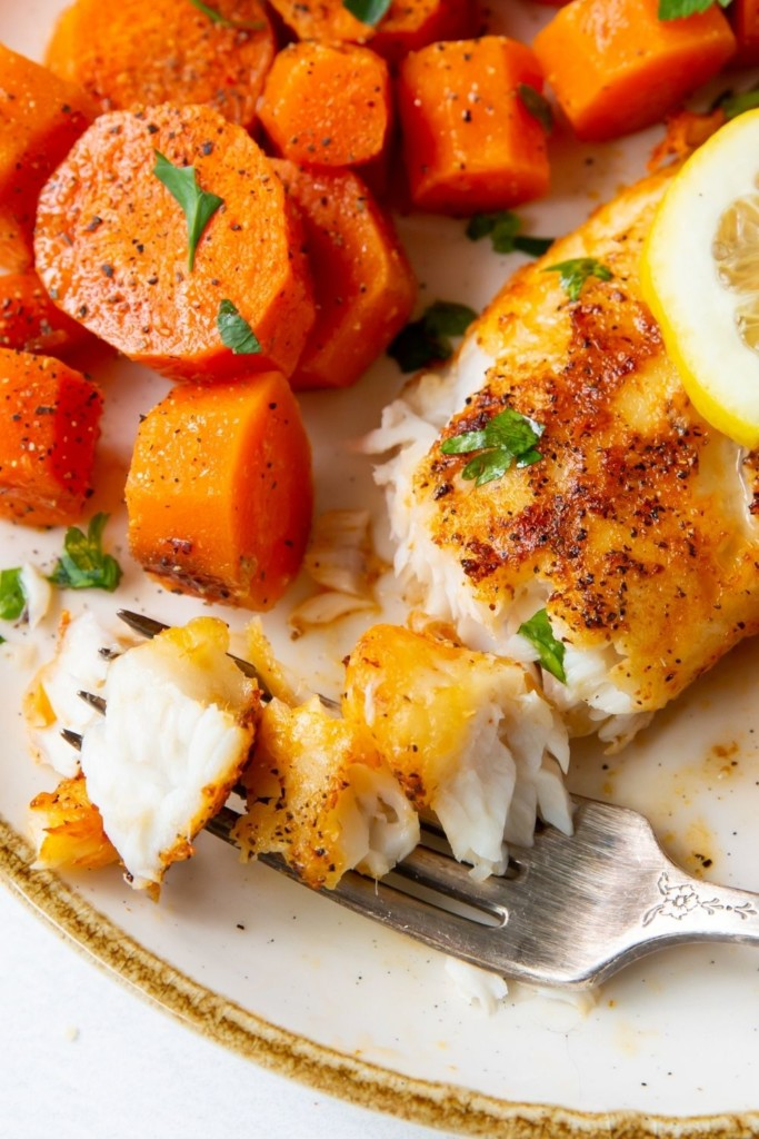 Closeup of flaked tilapia on a fork served on a white plate with carrots