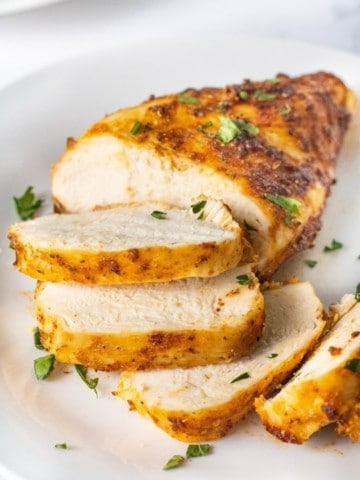 Closeup of sliced air fryer chicken breasts that were cooked from chicken on a white plate