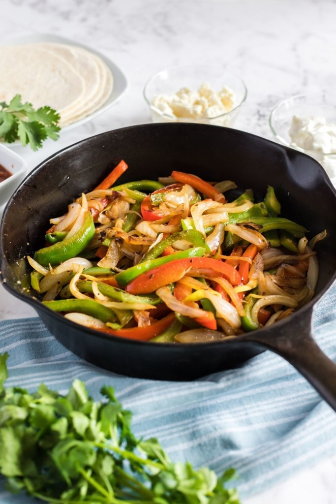 Sauteed peppers and onions inside a cast iron skillet