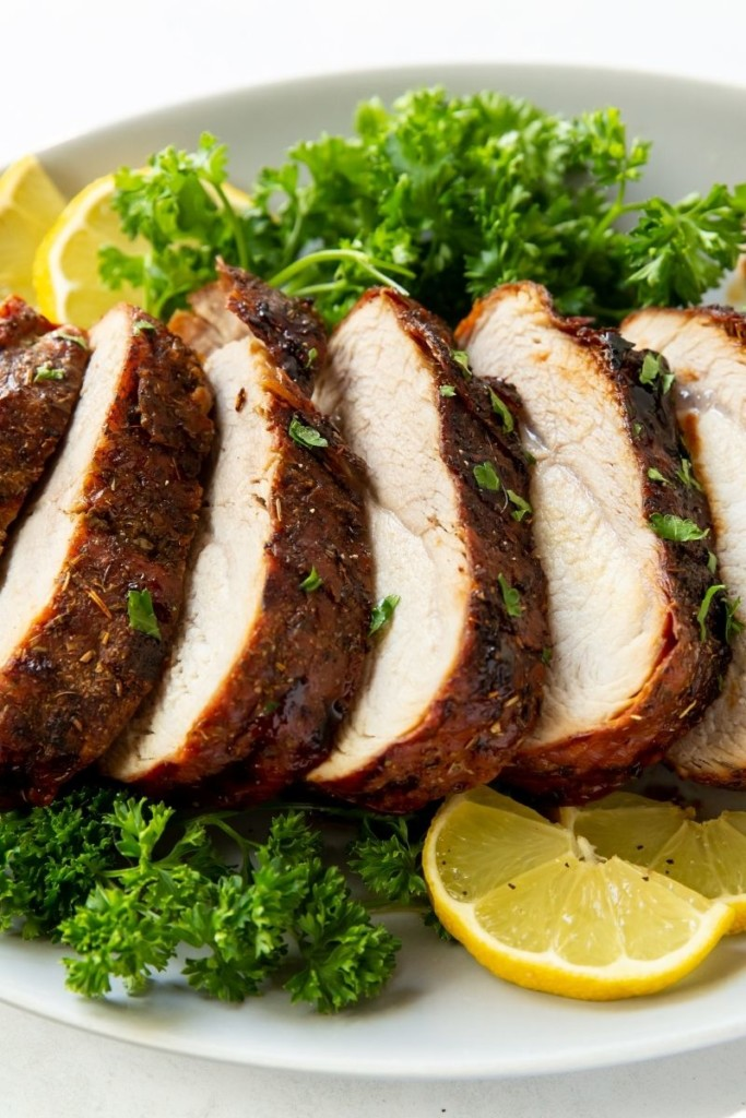 Closeup of Air Fryer Pork Loin sliced with parsley and lemons on a white plate