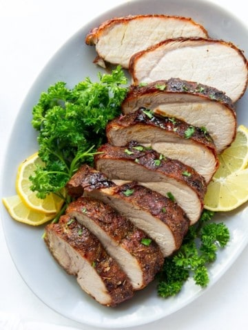 Air Fryer Pork Loin sliced on a plate with parsley and lemons