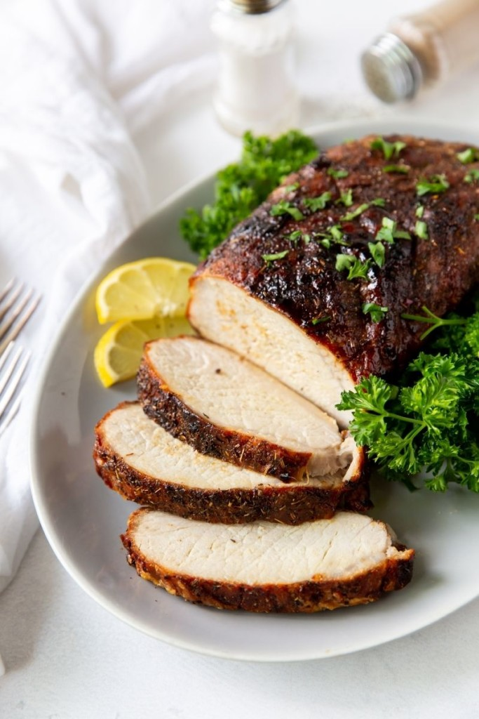 Pork loin on a serving platter with a few slices made with parsley and lemons