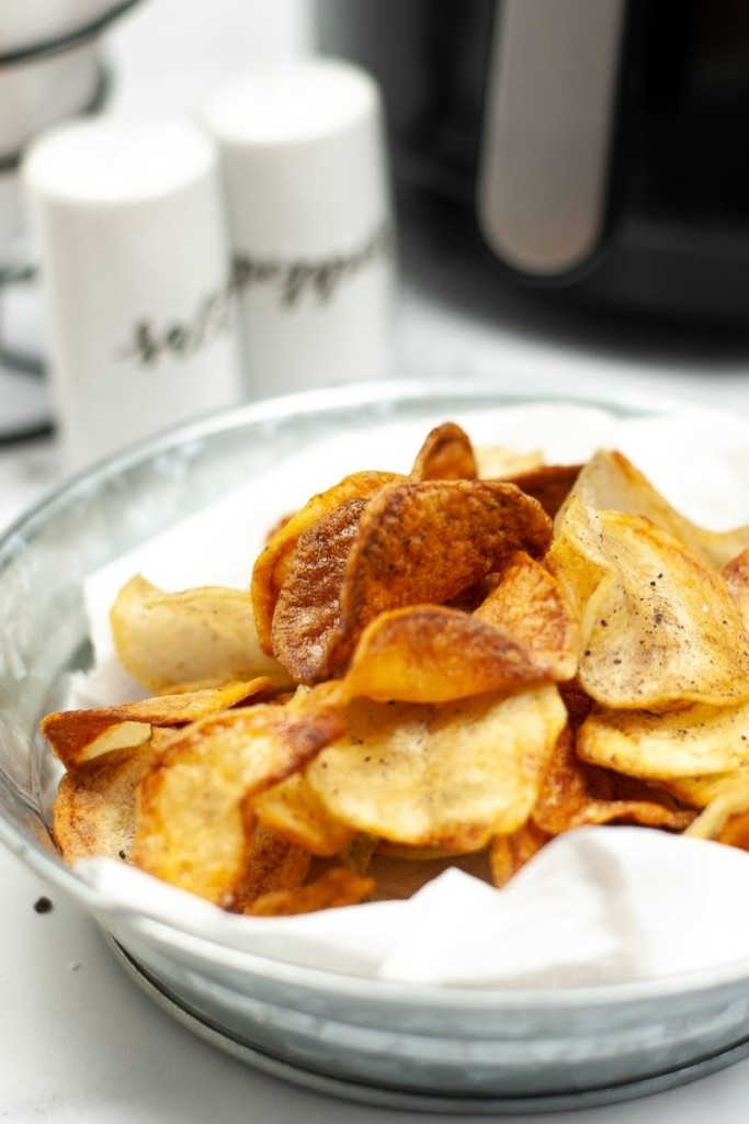 Air Fryer Potato Chips in a bowl with salt, pepper, and an air fryer in the background