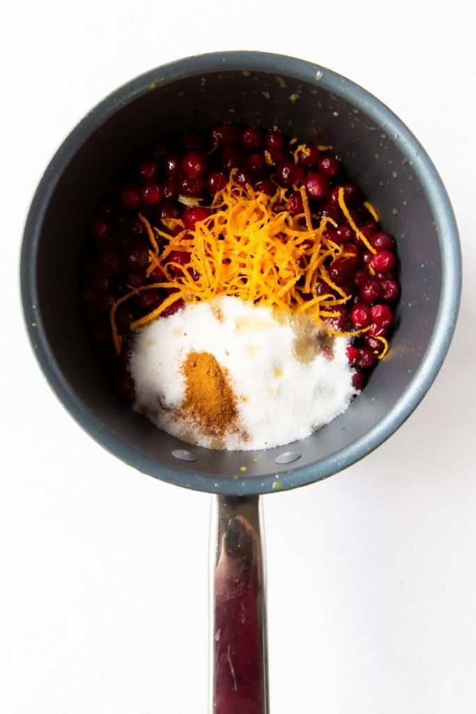 Cranberry sauce ingredients put into a saucepan on a white background