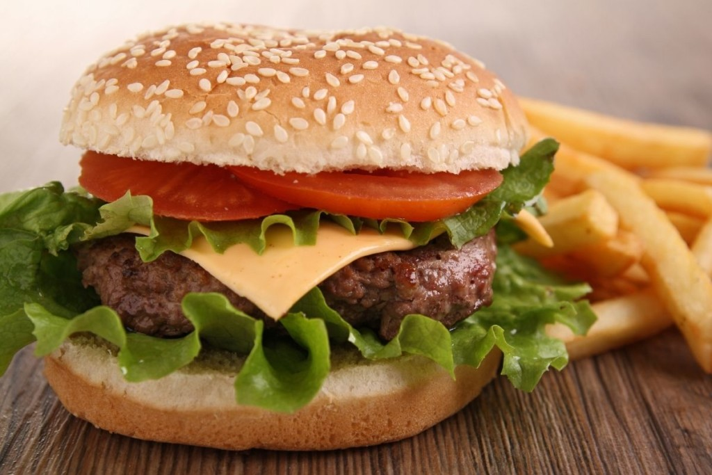 Cheeseburger on a sesame bun with lettuce and tomato on it with french fries in the background