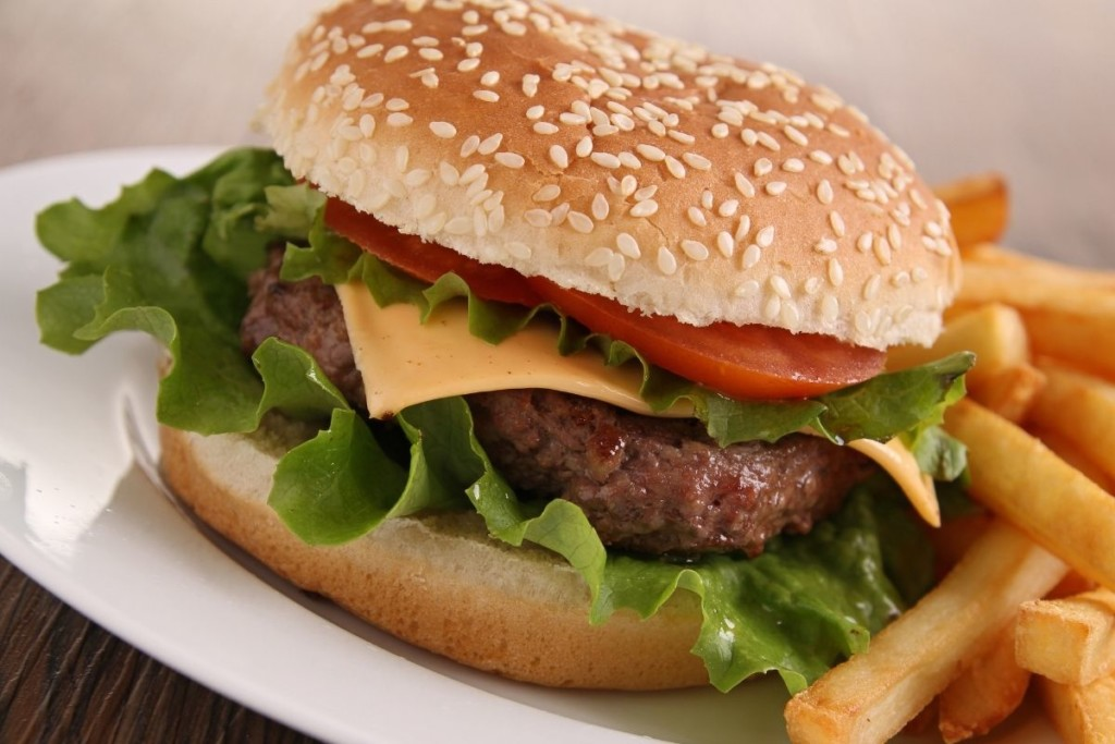 Hamburger on a sesame bun with cheese, lettuce, and tomato next to french fries