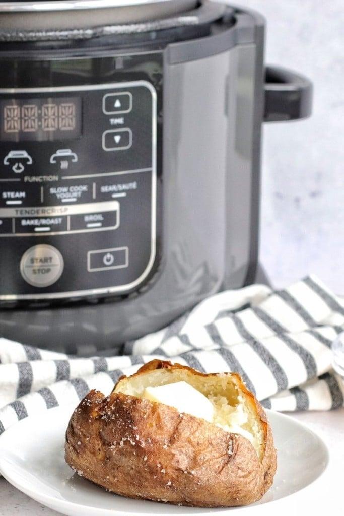 Cut open baked potato in front of a Ninja Foodi