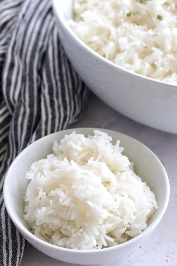 Ninja Foodi Rice in a small white bowl with a large serving bowl with rice in the corner
