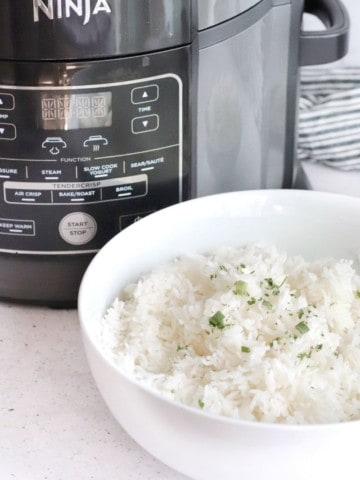 Rice in a white bowl in front of the Ninja Foodi