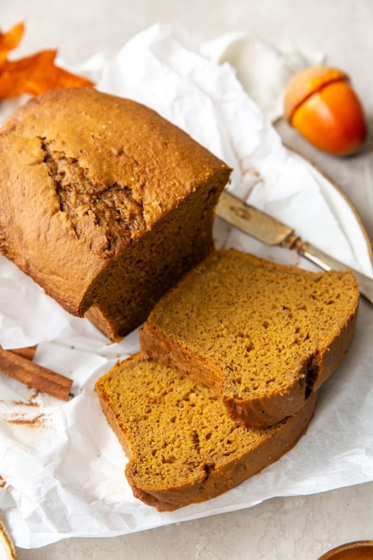 Cake mix pumpkin bread loaf with 2 slices cut laying on parchment paper