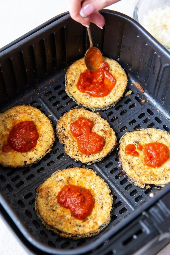 Eggplant parm in the air fryer being topped with sauce