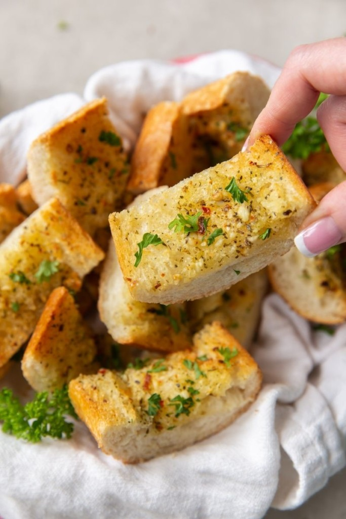 Hand picking up a piece of garlic bread from a basket