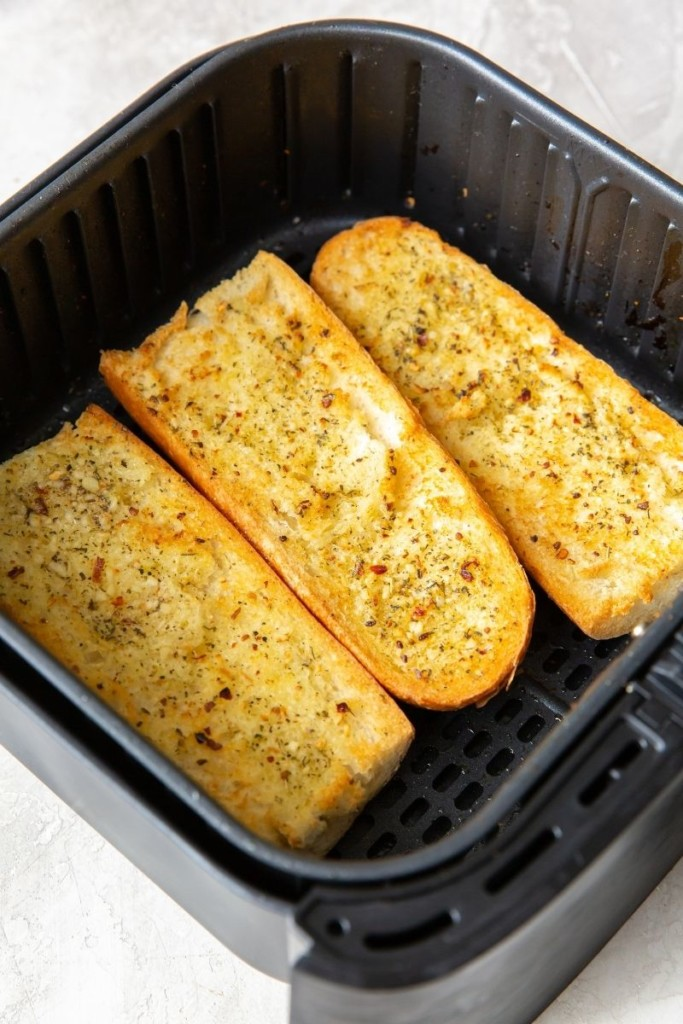3 halves of garlic bread inside the air fryer cooked
