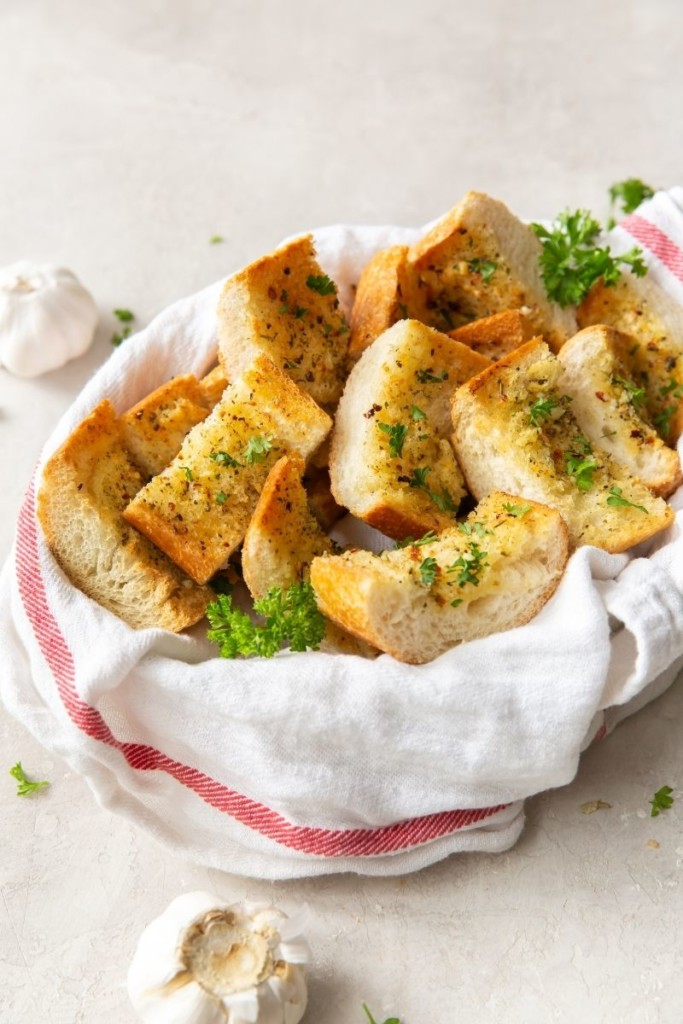 Air Fryer Garlic Bread slices inside a basket with garlic bulbs around it