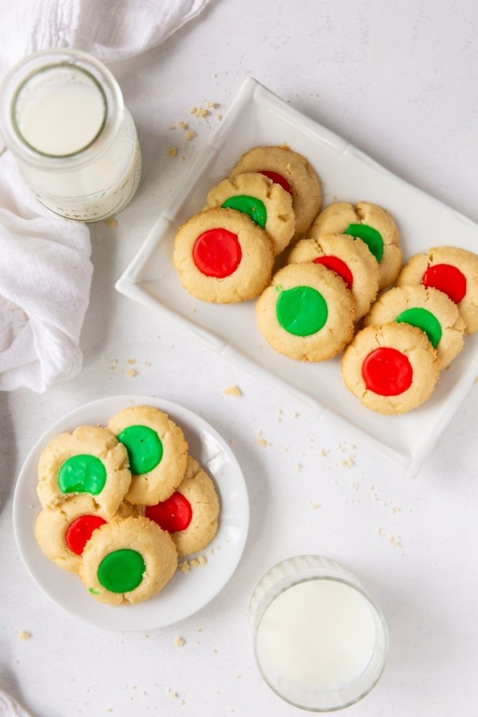 Overhead shot of 2 plates of cookies and glasses of milk on a white background