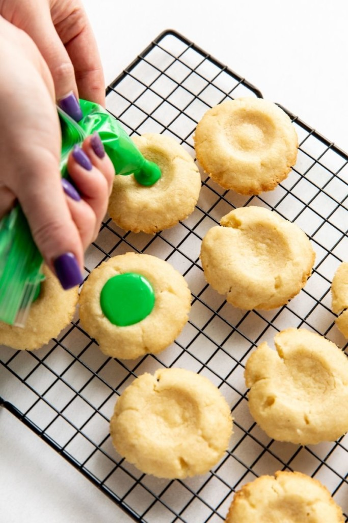 Piping green icing onto the cooked cookies