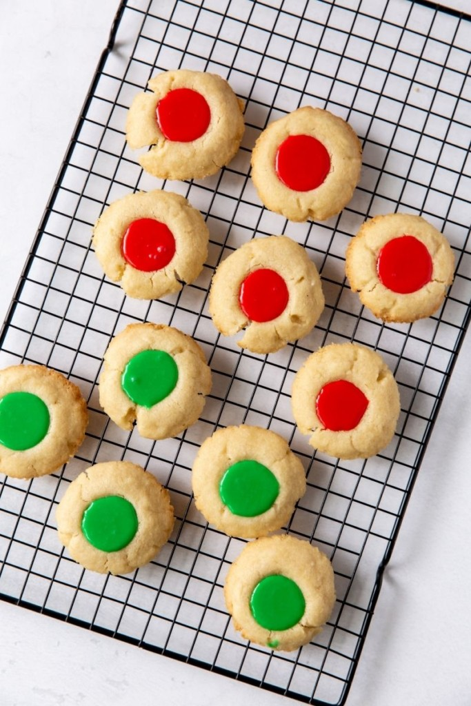 Iced Thumbprint Cookies with red and green icing on a cooling rack
