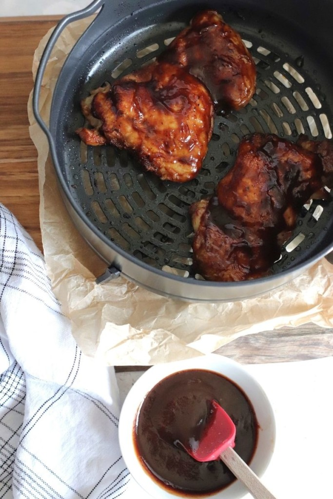 Fully cooked BBQ chicken thighs in Ninja Foodi with a bowl of BBQ sauce and basting brush