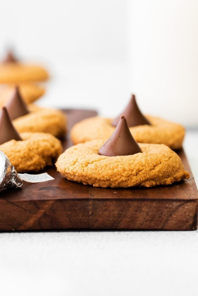 Closeup of peanut butter cookies with hershey kisses in the middle from the side on a brown cutting board