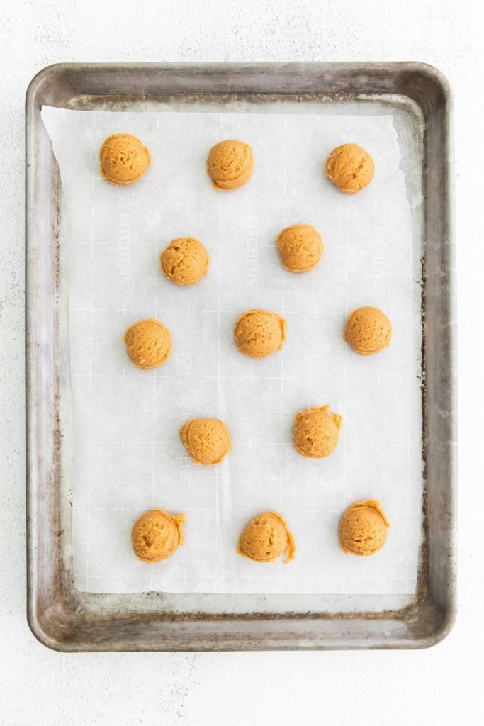 Scoops of cookie dough on a baking sheet with parchment paper