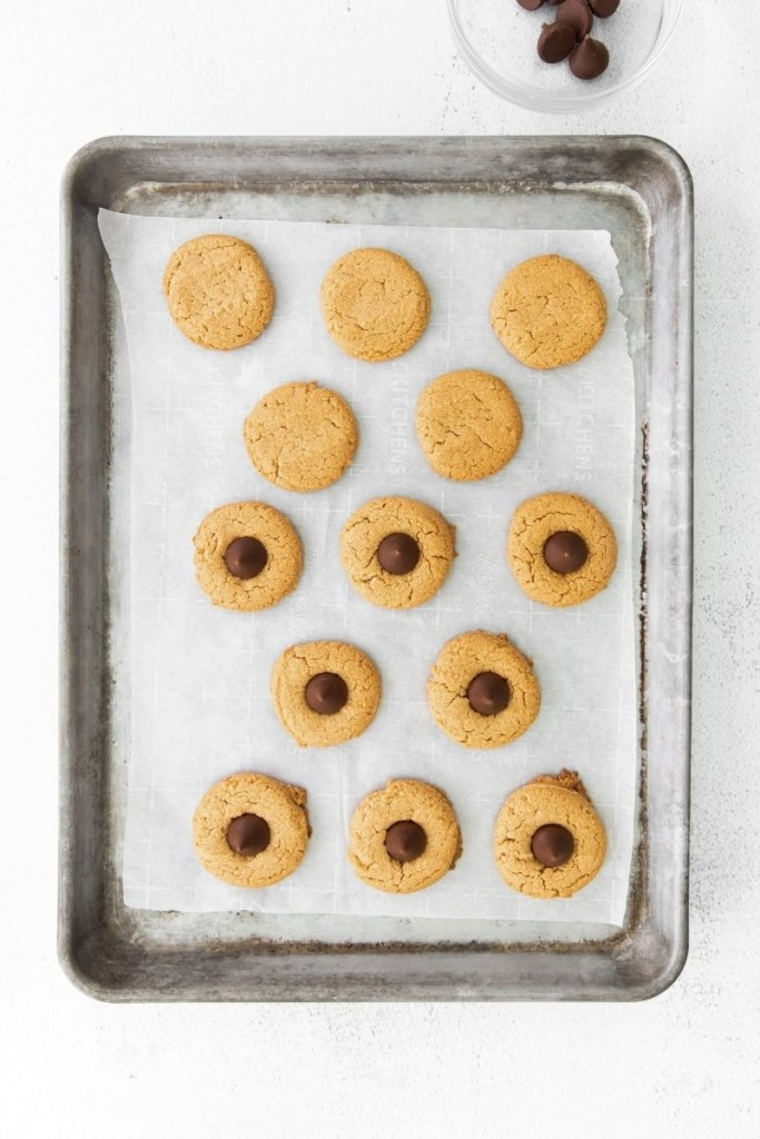 Baked cookies on a baking sheet half topped with Hershey kisses in the middle