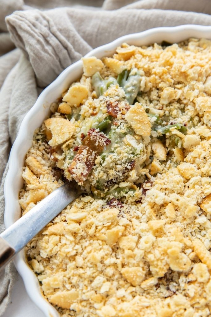 Green Bean Casserole in a round casserole dish with a serving spoon inside