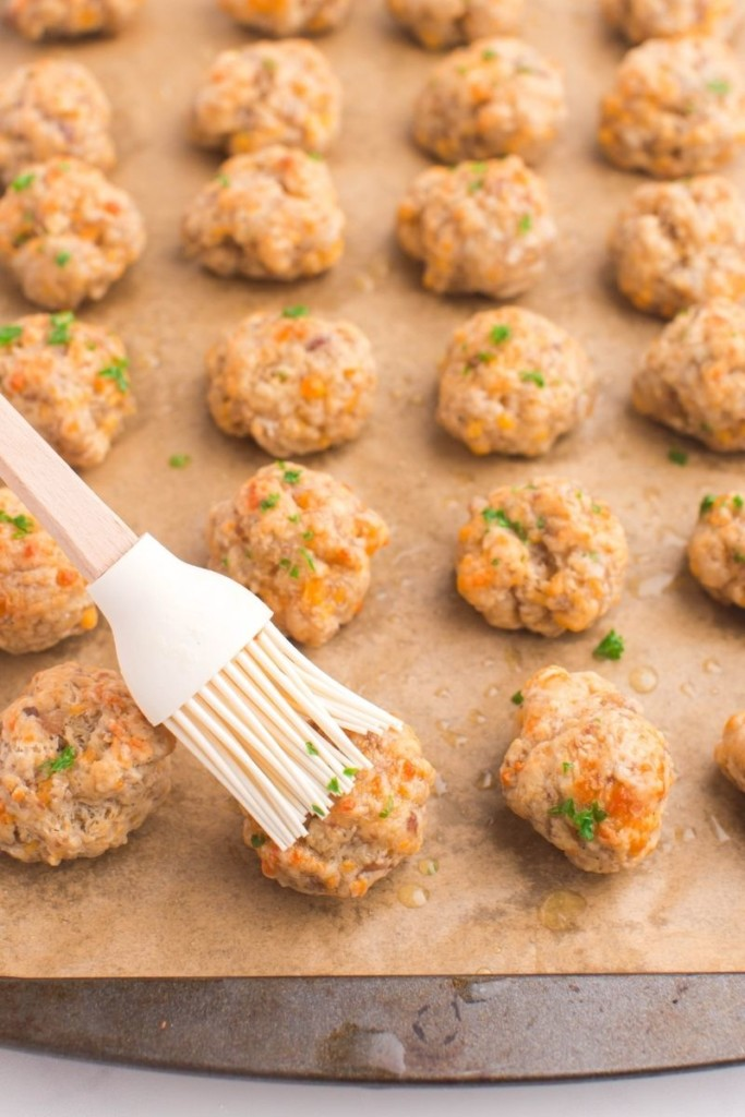 Cooked sausage balls being pasted with butter on a baking sheet