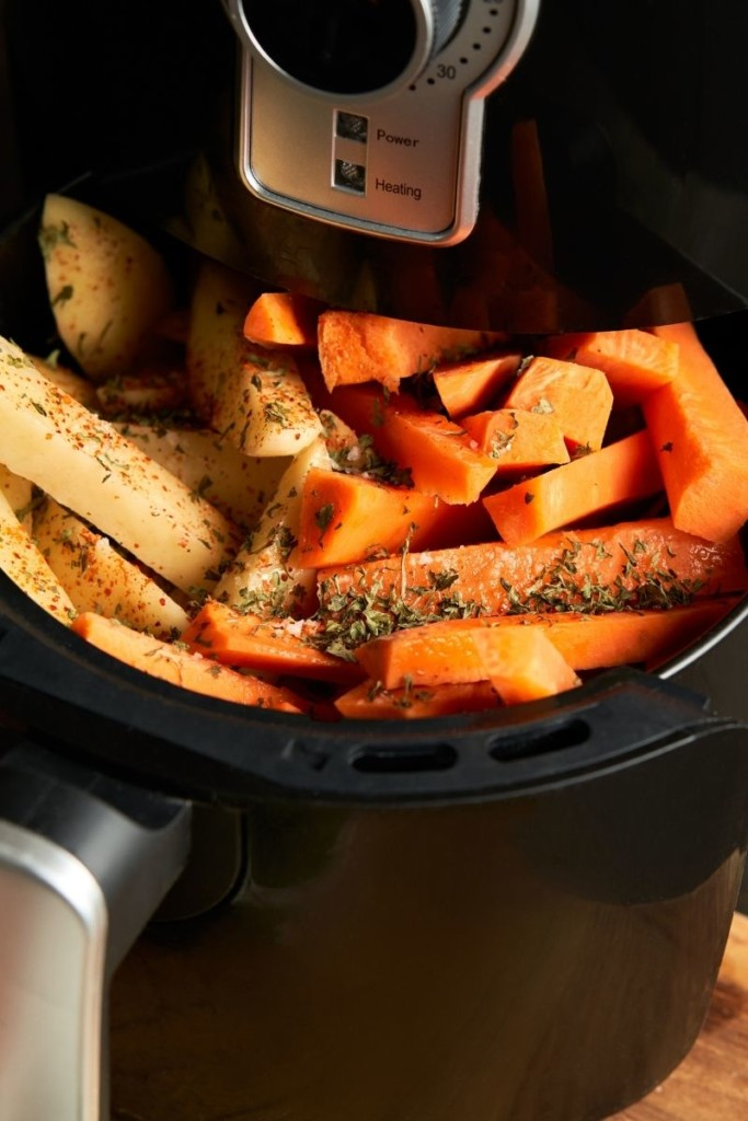 Small air fryer filled with carrots and potatoes
