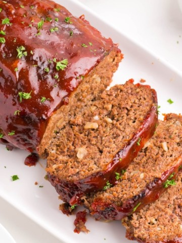 Air Fryer Meatloaf on a white serving tray with half sliced