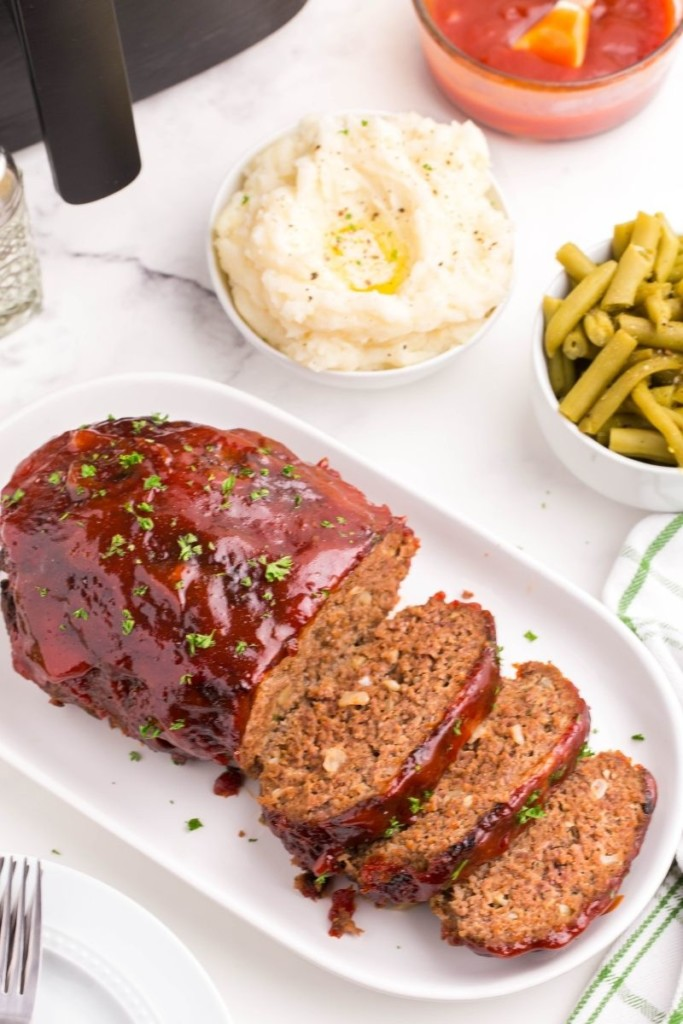 Sliced air fryer meatloaf on a serving tray with mashed potatoes and green beans in bowls in background