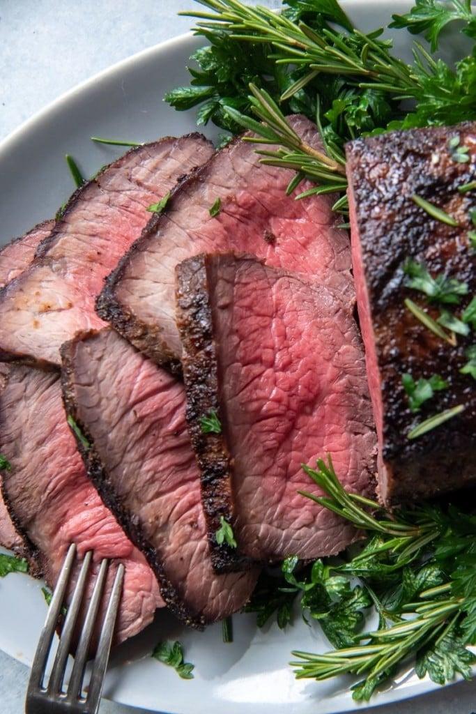 Closeup of sliced air fryer roast beef on a serving platter