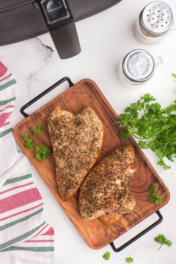 Cooked full air fryer turkey tenderloins on a wooden serving tray